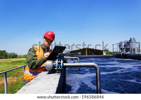 Worker inspecting valve for filtering water. Focus on Valve. - stock photo