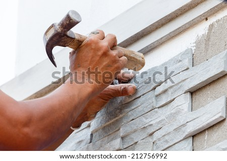 worker install stone wall surface with cement for house  - stock photo