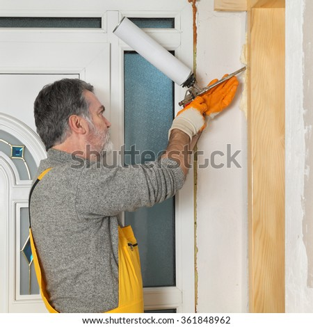 Worker install wooden door, using polyurethane foam to fix it at wall, home renovation - stock photo