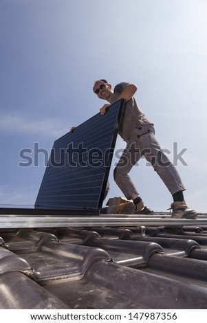 worker installing alternative energy photovoltaic solar panels on the roof of a single family house - stock photo