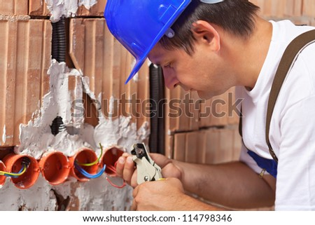Worker installing electrical wires in a new building wall - closeup - stock photo