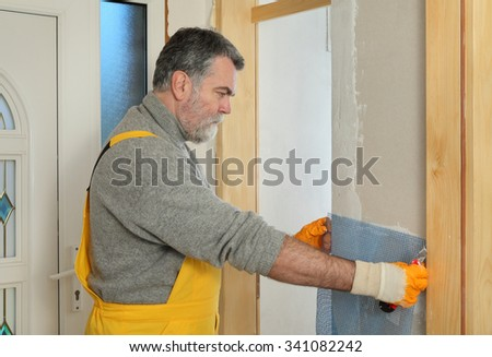 Worker installing gypsum board, placing mesh to wall - stock photo