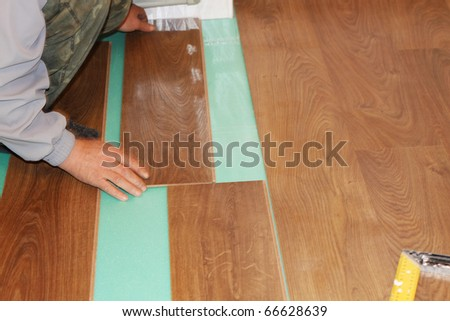 worker installing new laminate flooring - stock photo