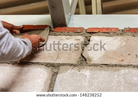 Worker installing red brick with trowel for wall of room in house