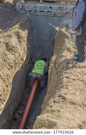 Worker installing sewer pvc pipe in trench - stock photo