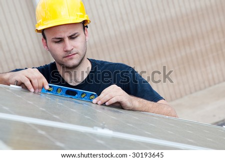Worker installing solar panels uses a level to check that the angle is right. - stock photo