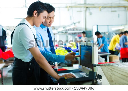 Worker is new assigned to a machine in a textile factory, the foreman explains something - stock photo