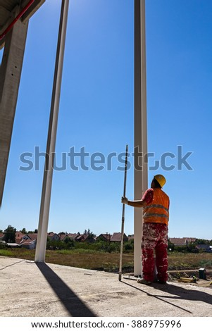 Worker is painting tall steel pillar with paint brush at construction site. - stock photo