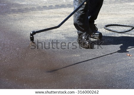 Worker is spraying the black hot asphalt at a road construction.