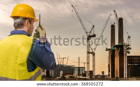 Worker is using radio and crane site. Construction concept. - stock photo