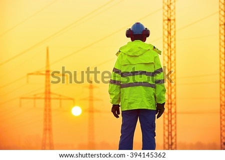 Worker is watching electricity pylons and substation at the sunrise