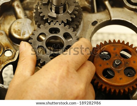 worker keeps a gear in overalls, is photographed by a close up