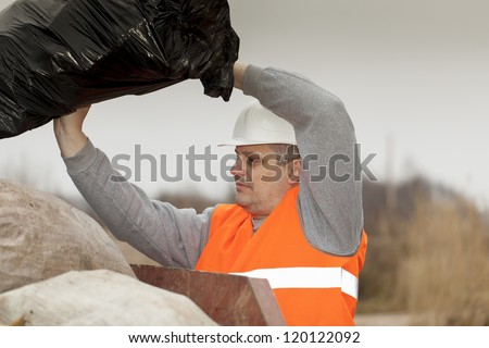 Worker keeps garbage bag near container - stock photo