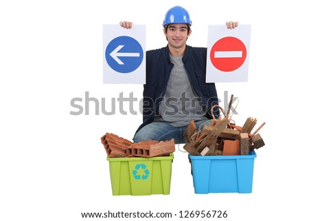 Worker kneeling by recycle boxes - stock photo