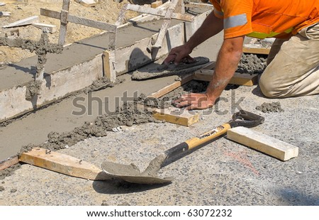 Worker laying concrete curb with spreader - stock photo