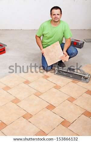 Worker laying floor tiles on concrete surface in a new building - stock photo