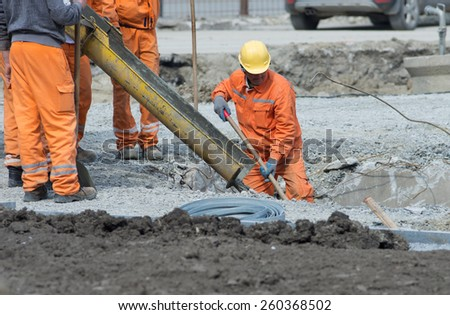 Worker leveling concrete poured from mixer on construction site - stock photo