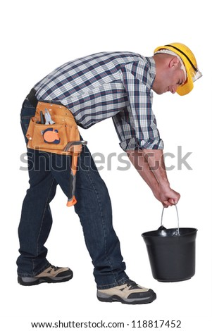 Worker lifting plastic bucket - stock photo