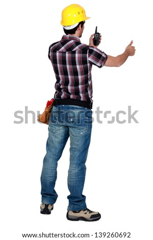 Worker looking at his walkie talkie - stock photo