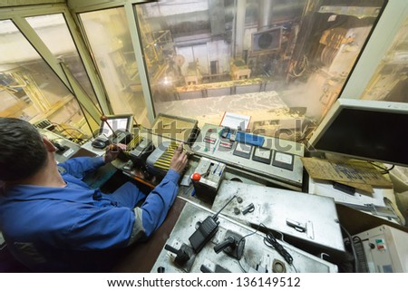 Worker looking on the left in control cabin of rolling mill. - stock photo