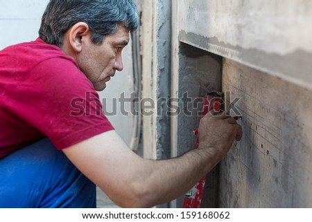 Worker makes the calculations in a niche for radiators in apartment with a rough finish - stock photo