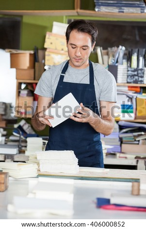 Worker Making Notebooks In Factory - stock photo
