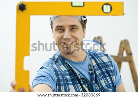 Worker measuring with square level tool, smiling. Isolated on white background. - stock photo