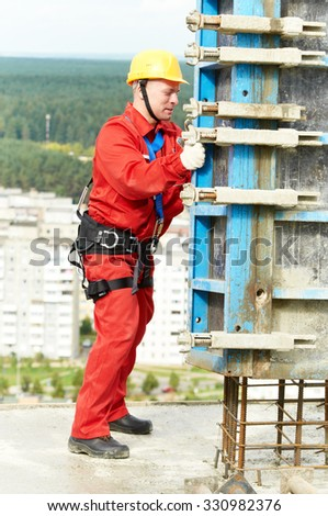 worker mounter concreter installing concrete formwork at construction site  - stock photo