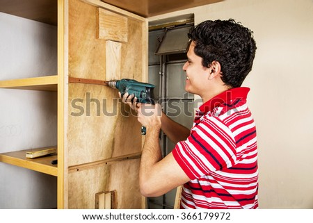 Worker of the construction arming a wood closet - stock photo