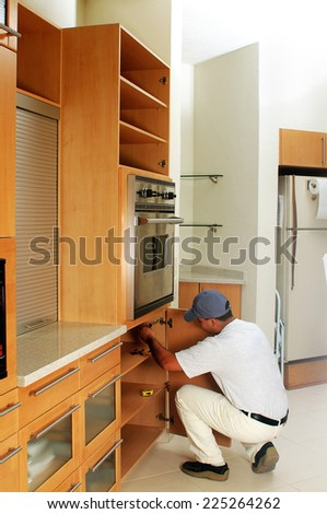 Worker of the construction arming an integral kitchen - stock photo