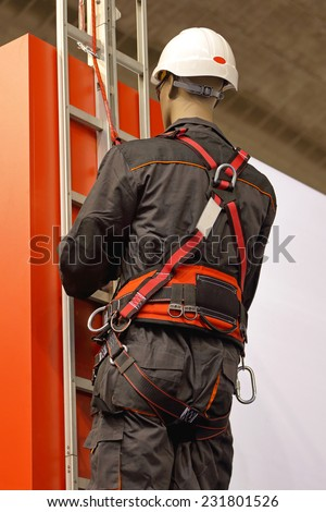 Worker on a ladder uses a safety harness to prevent falling from the building - stock photo