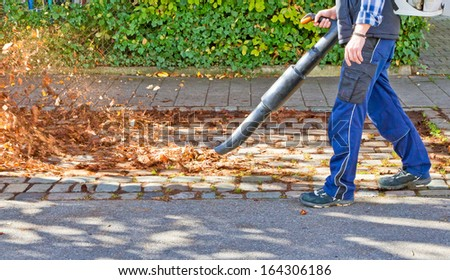 Worker on a street in autumn with a leaf blower - stock photo