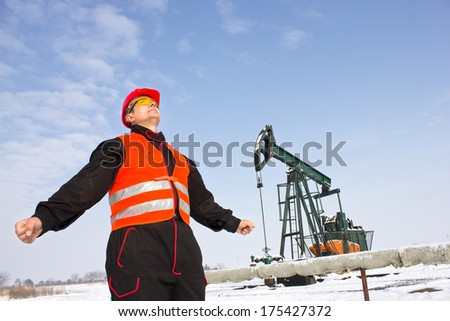 worker on an oil pump stands with open arms,best focus on the orange vest