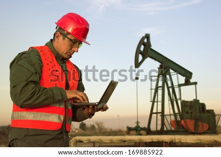 worker on an oil rig using a laptop, best focus on the man, background soft focus - stock photo