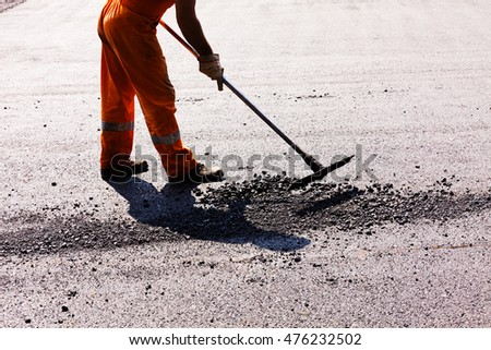 Worker on asphalting the road