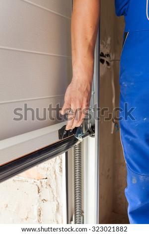 Worker open a garage door during installation - stock photo