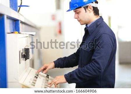 Worker operating a machine in a factory  - stock photo