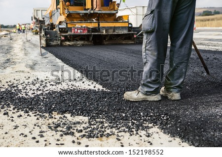 Worker operating asphalt paver machine during road construction and repairing works - stock photo