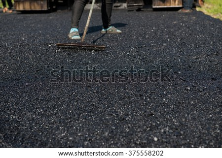 Worker operating asphalt paver machine during road construction and repairing works focus on asphalt road