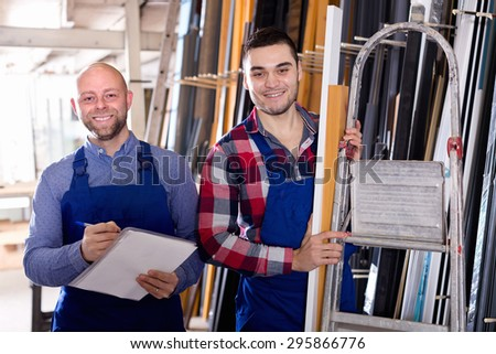 Worker operating in lathe, his boss with papers nearby