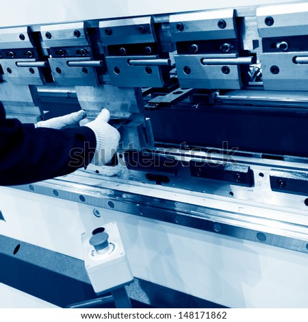 worker operating metal press machine at workshop.  - stock photo