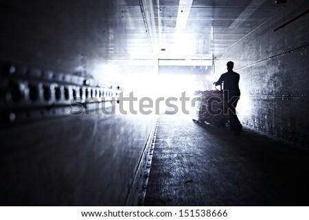 Worker operating pallet lifter on dark warehouse - stock photo