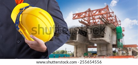 worker or engineer holding in hands yellow helmet for workers security on the background motorway construction with beautiful sky - stock photo