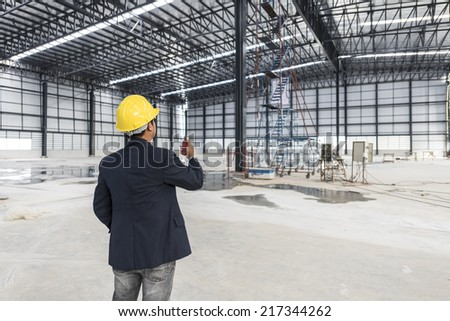 worker or engineer with yellow helmet for workers security holding radio communication in a construction site warehouse - stock photo