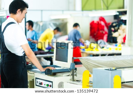Worker or production manager at a screen of a large machine in a textile factory in Asia - stock photo