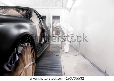 worker painting a black car in a special garage, wearing a white costume