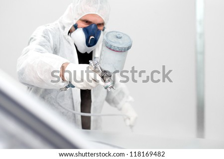 worker painting a car in a special painting box - stock photo