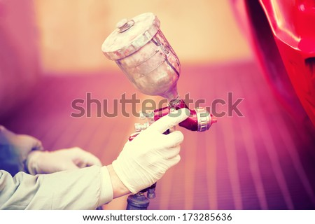 Worker painting a red car in painting booth using professional tools and spray gun - stock photo