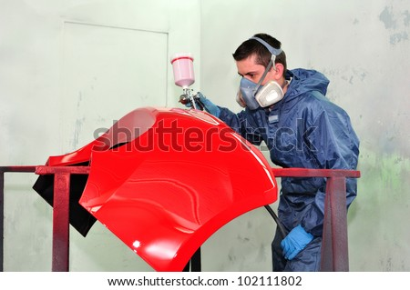 Worker painting a red fender. - stock photo