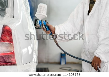 worker painting a white car - stock photo